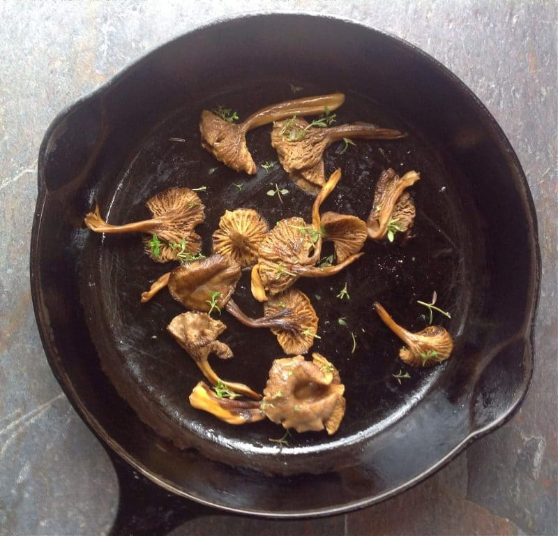 cooked yellowfoot chanterelles with thyme in a cast iron skillet