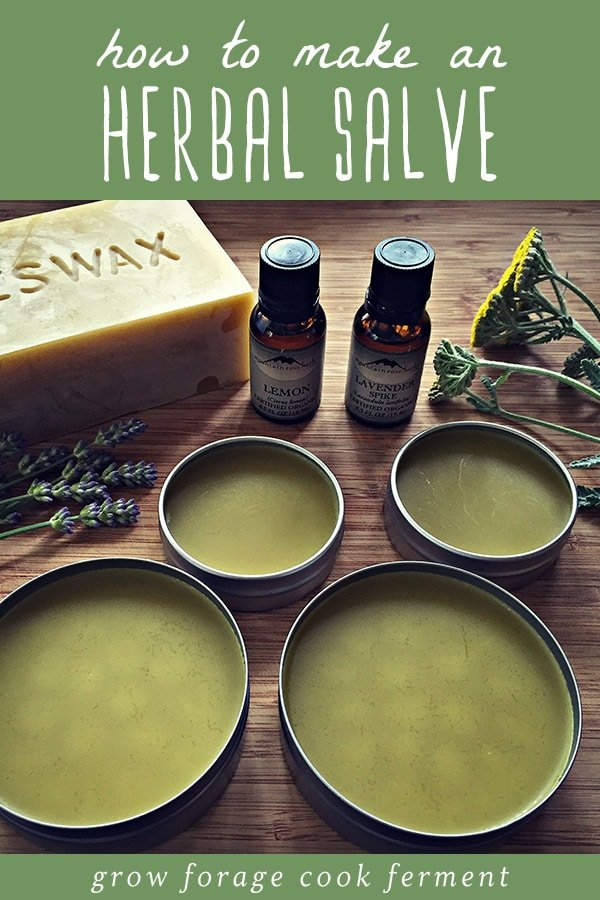 Several tins of homemade herbal salve with a bar of beeswax, essential oils, and herbs in the background.