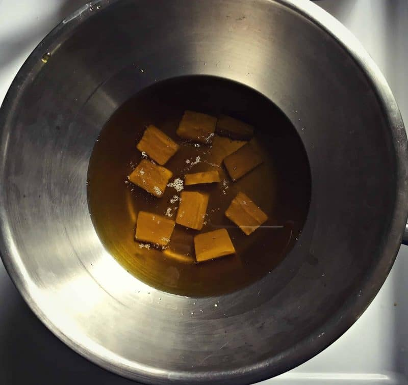 melting beeswax into infused oil with a double boiler