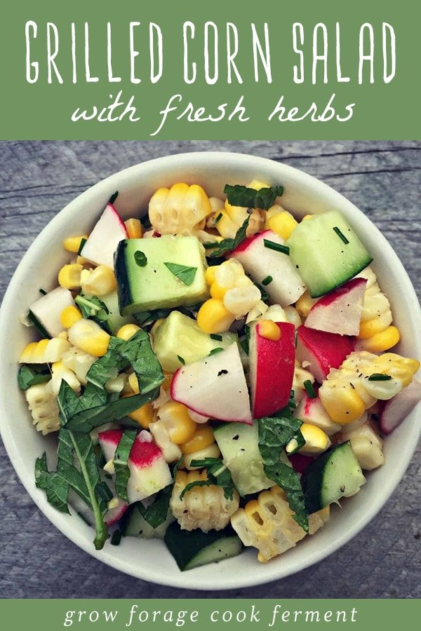 A bowl of grilled corn salad with cucumbers, radishes, and fresh herbs on a wood table.