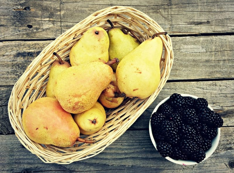 a basket of pears and a bowl of blackberries