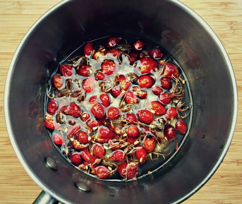 rose hips covered in water in a pan