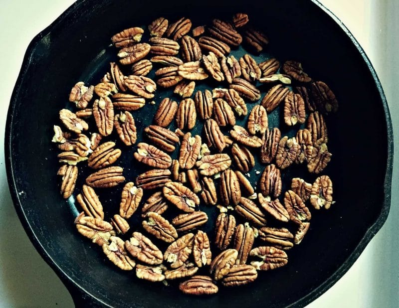pecans roasting in a cast iron skillet