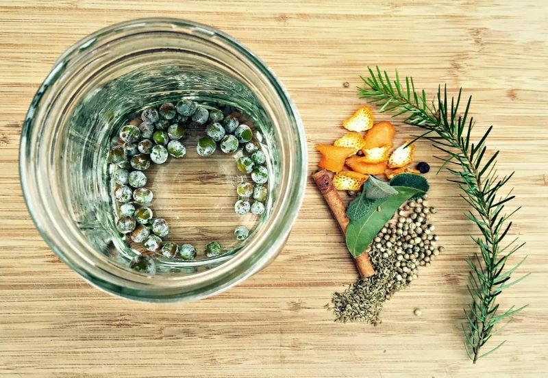 juniper berries in vodka and herbs on a table