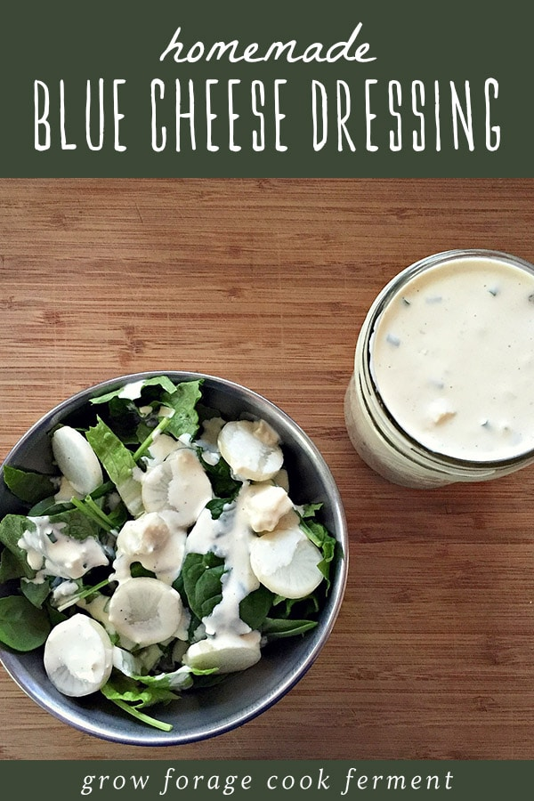 A bowl of salad dressed with homemade blue cheese dressing, and a mason jar of homemade blue cheese dressing.