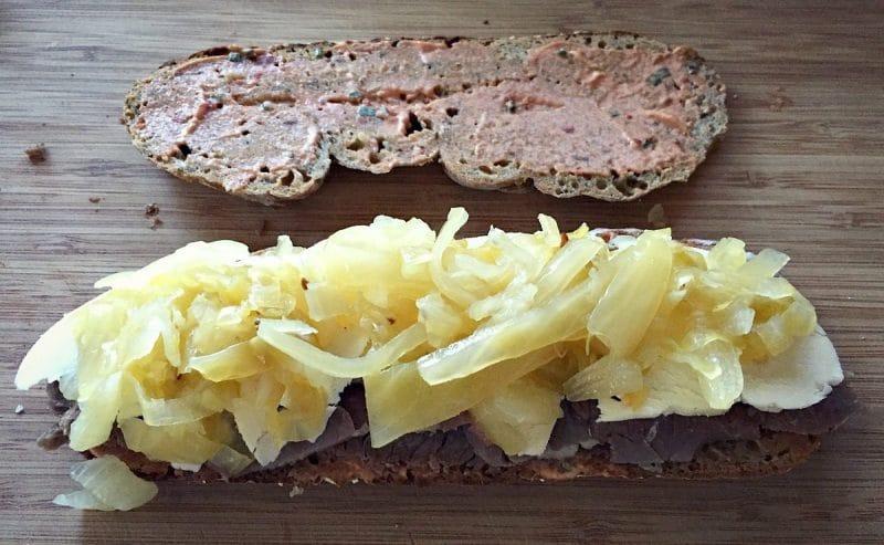 assembling the reuben sandwich with sauerkraut