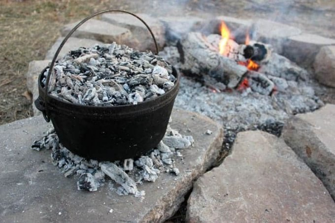Dutch oven on hot coals by a fire
