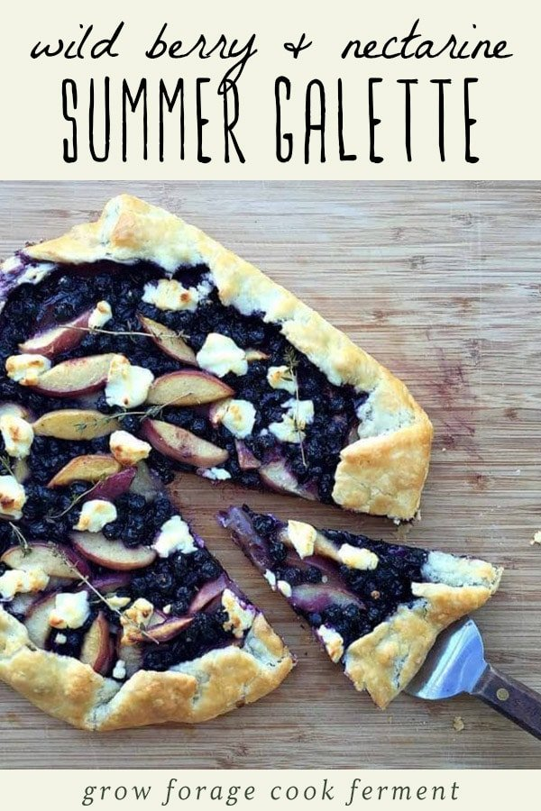 Wild berry nectarine galette with goat cheese on a wood cutting board.
