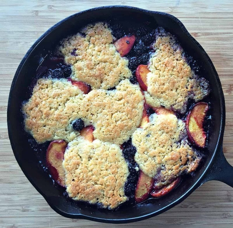 skillet peach blackberry cobbler on a table