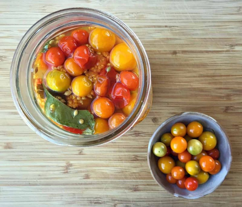fermented cherry tomatoes in a jar and bowl