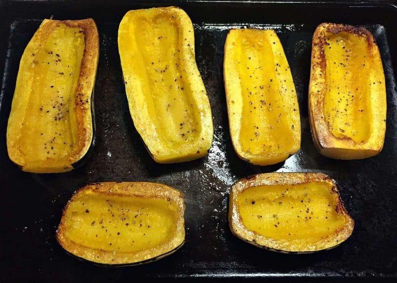 roasted delicata squash halves on a baking sheet