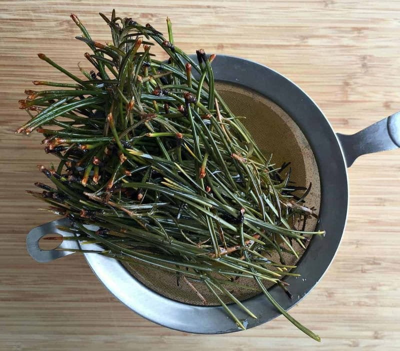 straining the pine and rosemary out of the oil