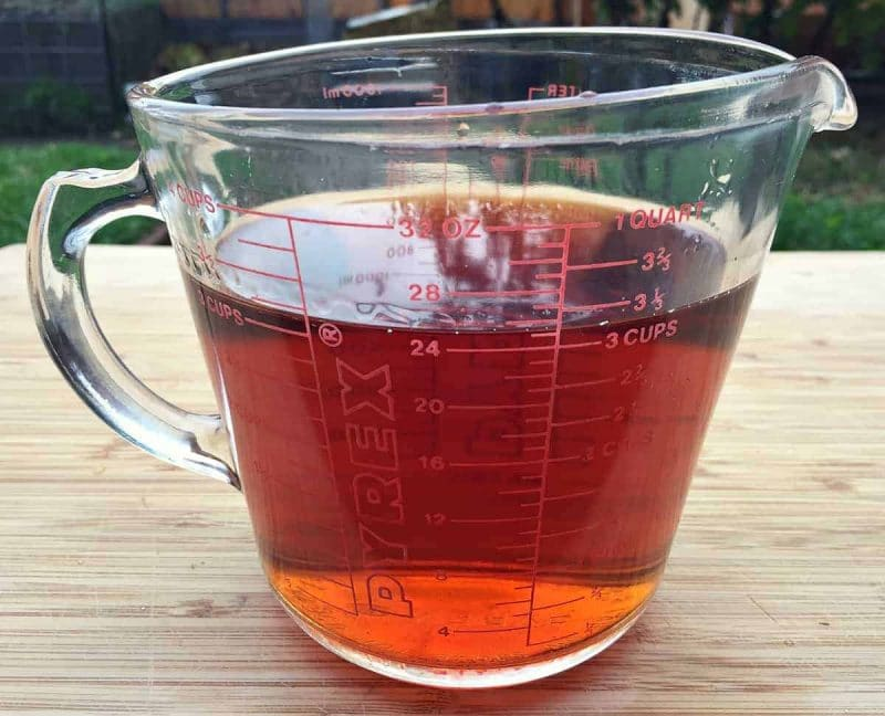 strained conifer infused vodka in a glass measuring cup