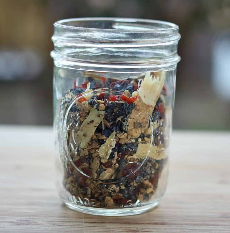 a mason jar of dried herbs and flowers for tea