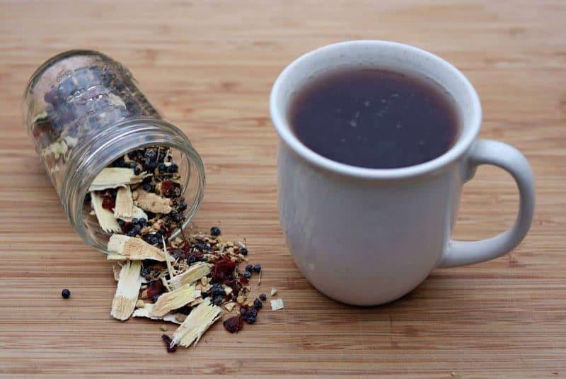 Herbal tea blend next to a mug of hot tea