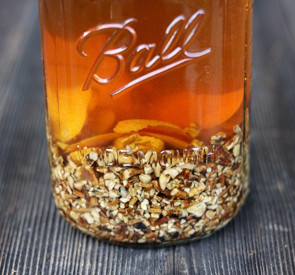 Mason jar of dandelion roots being infused in vodka