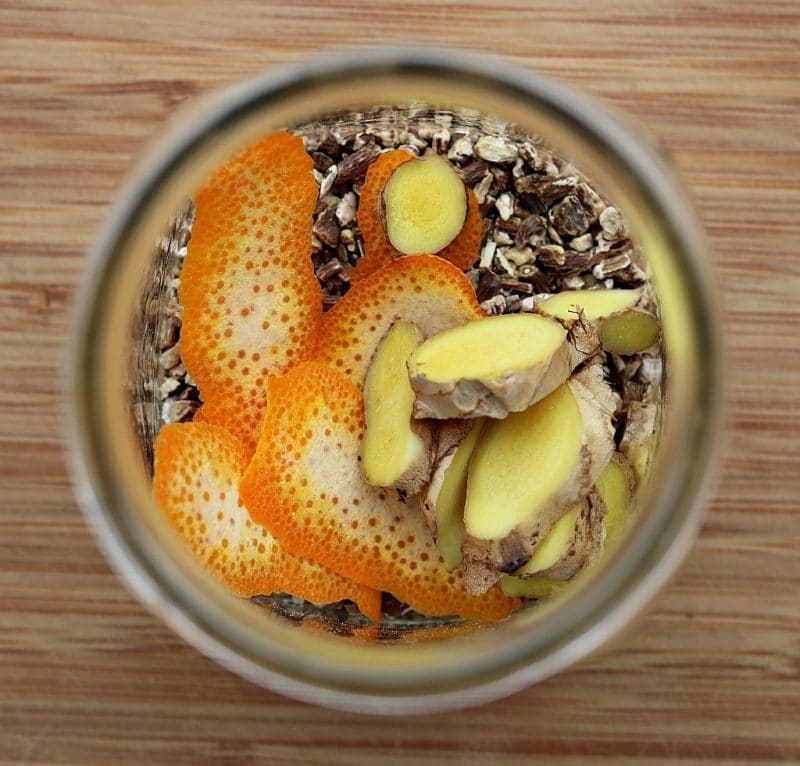 Looking into a mason jar filled with dandelion roots, ginger, and orange peel