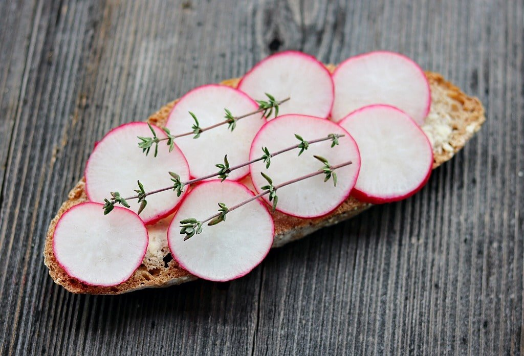 a slice of bread with butter, sliced radishes, and fresh thyme