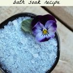 Homemade viola bath salt in a small bowl with a fresh viola flower.
