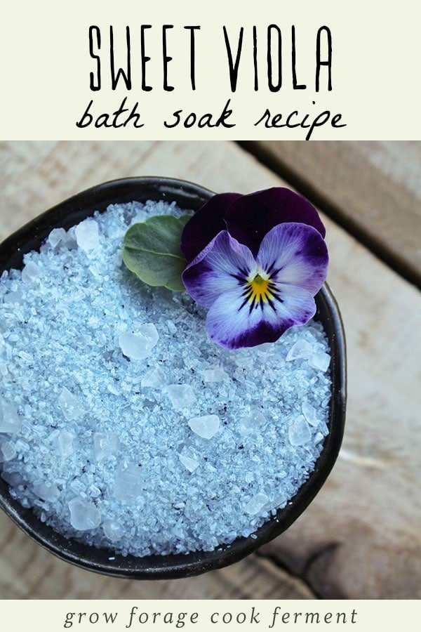 Homemade viola bath salt in a small bowl with a fresh viola flower.
