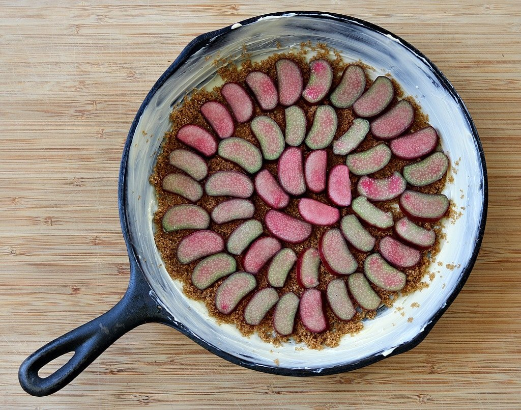 rhubarb slices in the bottom of a buttered cast iron skillet