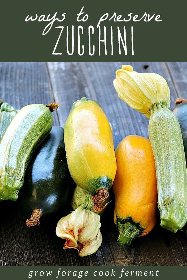 A variety of fresh zucchini on a wood table, ready to be preserved.
