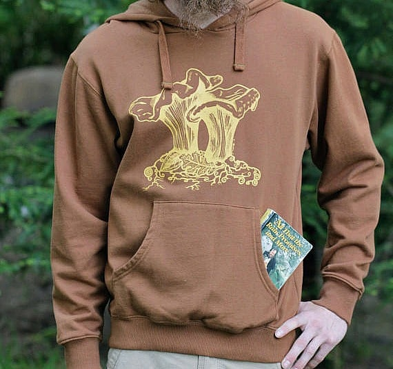 a man wearing a brown hoodie with a yellow chanterelle mushroom