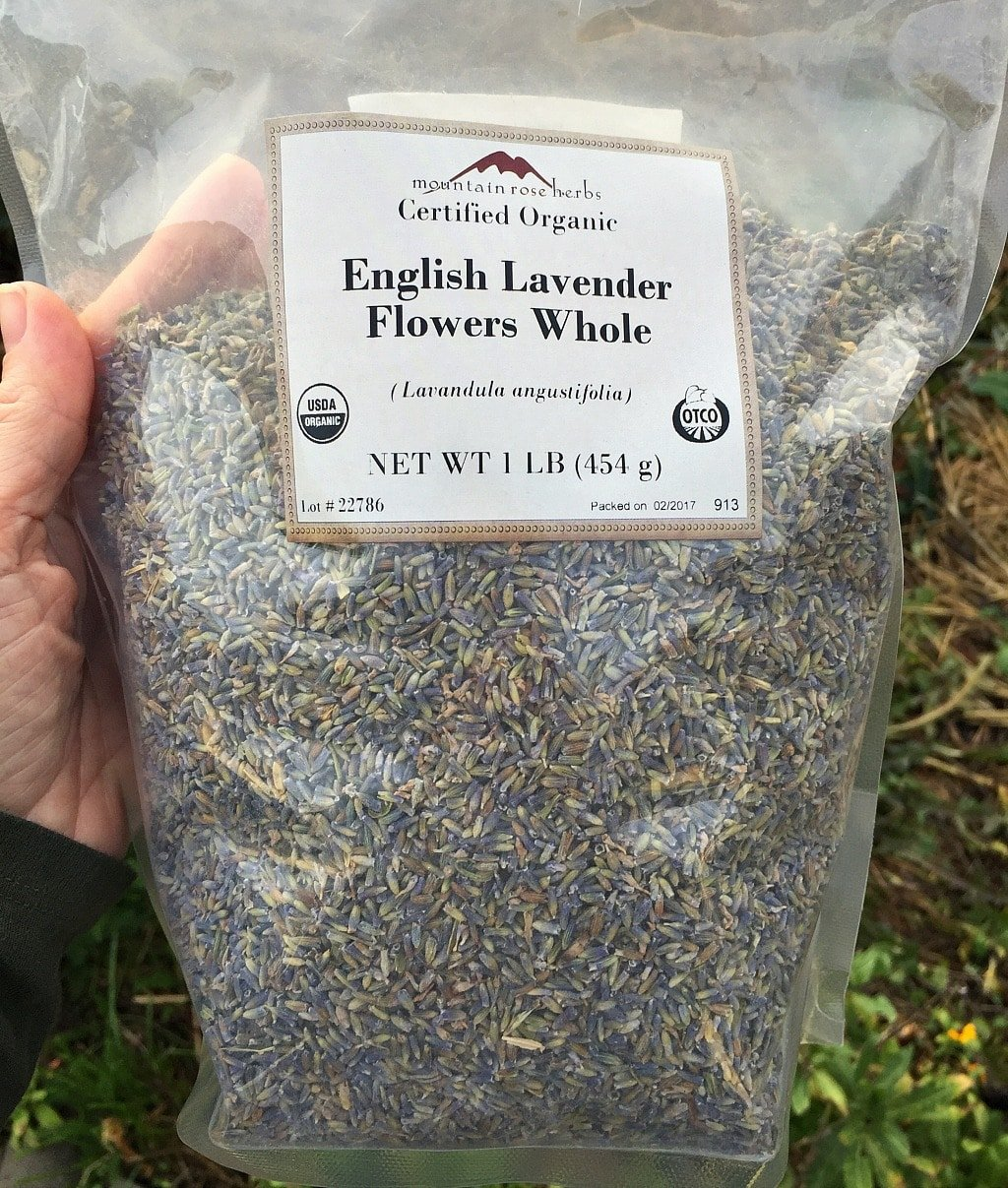 a hand holding a bag of Mountain Rose Herbs dried lavender flowers
