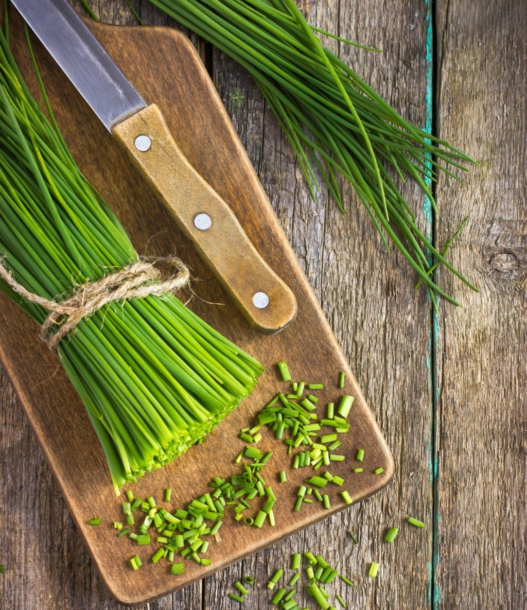 bunch of fresh chives on a wooden cutting board, top view