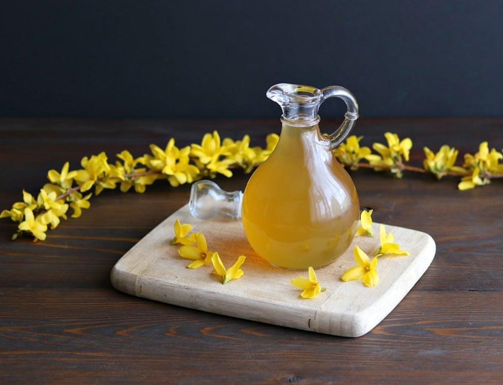 a small jug of forsythia syrup on a cutting board