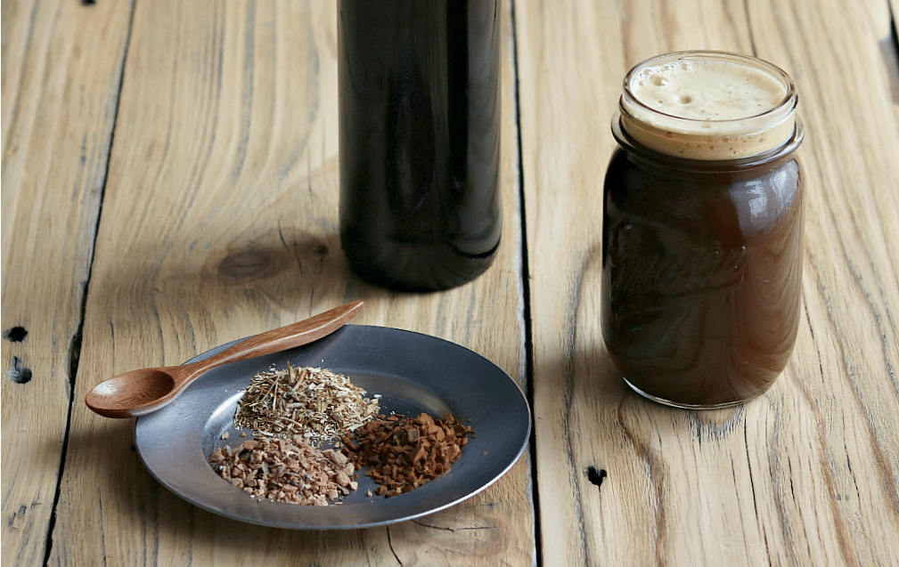 a glass of fermented root beer and a plate with dried roots and herbs