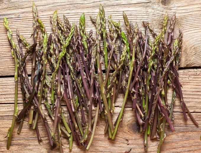 a bunch of purple and green asparagus on a wooden surface