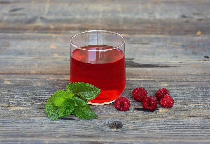 a glass of raspberry mint infused wine with a mint sprig and fresh raspberries