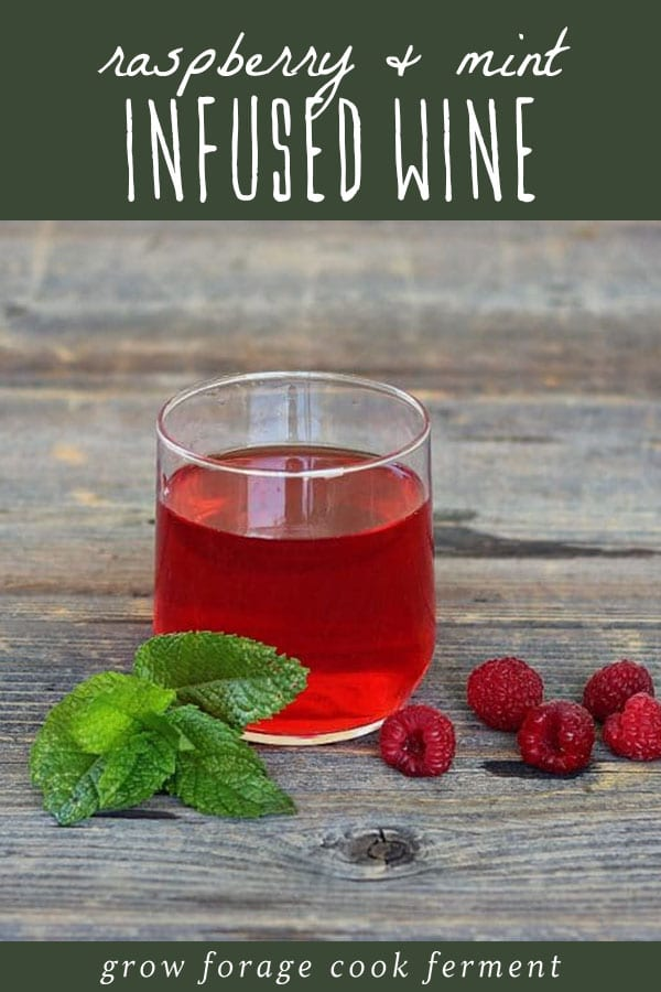 A glass of raspberry mint infused wine on a wood table.