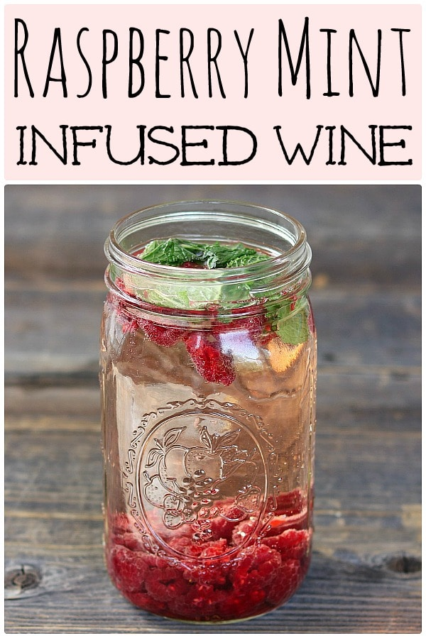 a quart jar filled with raspberries, mint, and white wine