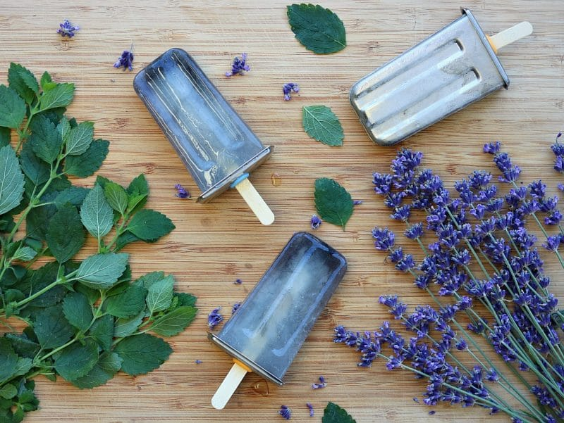 herbal popsicles on a board with fresh lavender and lemon balm