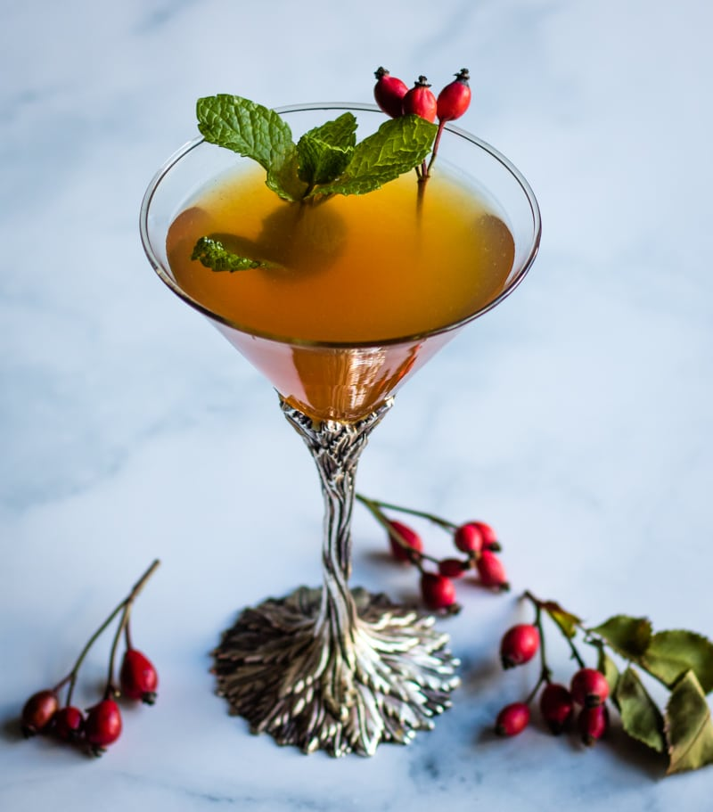 rose hip whiskey smash in a martini glass garnished with fresh mint and rose hips