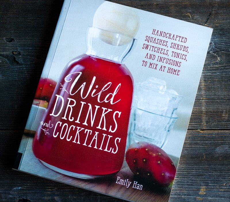 the book wild drinks and cocktails by emily han on a wooden board