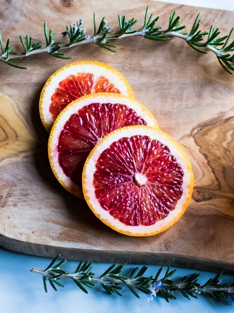 blood orange slices and rosemary on a wooden cutting board