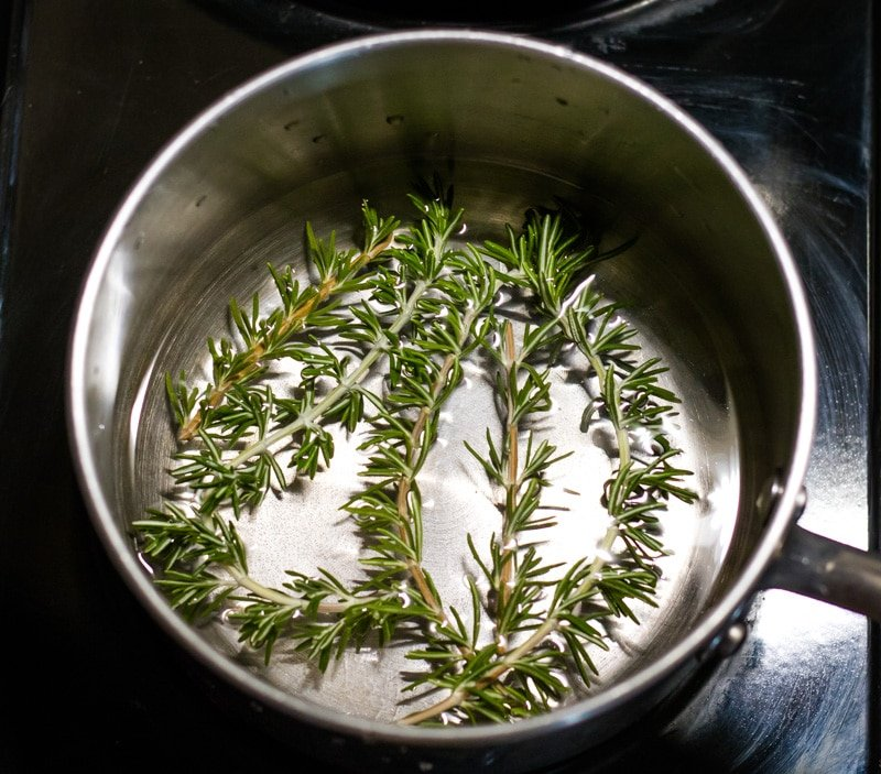 a pot with water and fresh rosemary sprigs