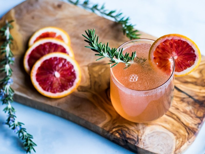 a glass of rosemary champagne cocktail with orange