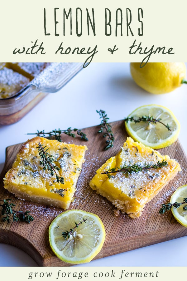 lemon bars with a sprig of thyme garnish on a wooden cutting board