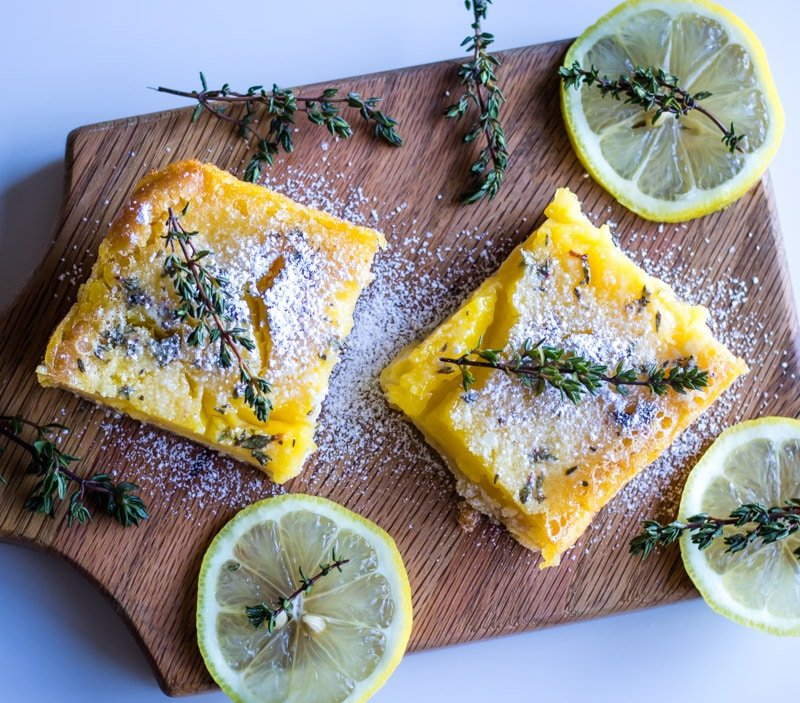lemon bars on wooden cutting board with lemon slices and fresh time
