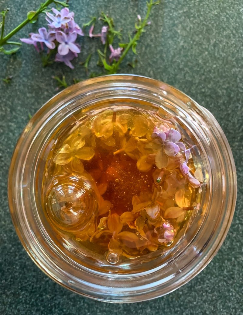 honey bubbling up in the jar with lilac flowers