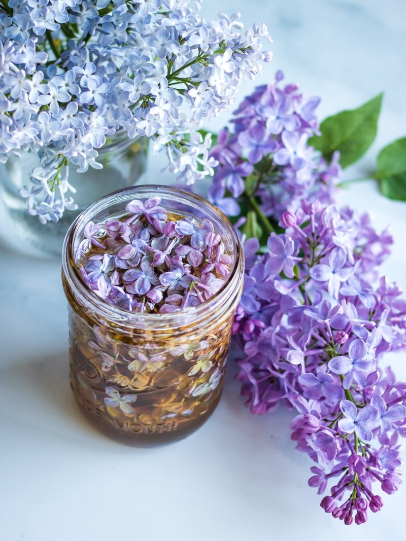 a jar of lilac flower honey with with and purple lilac blossoms