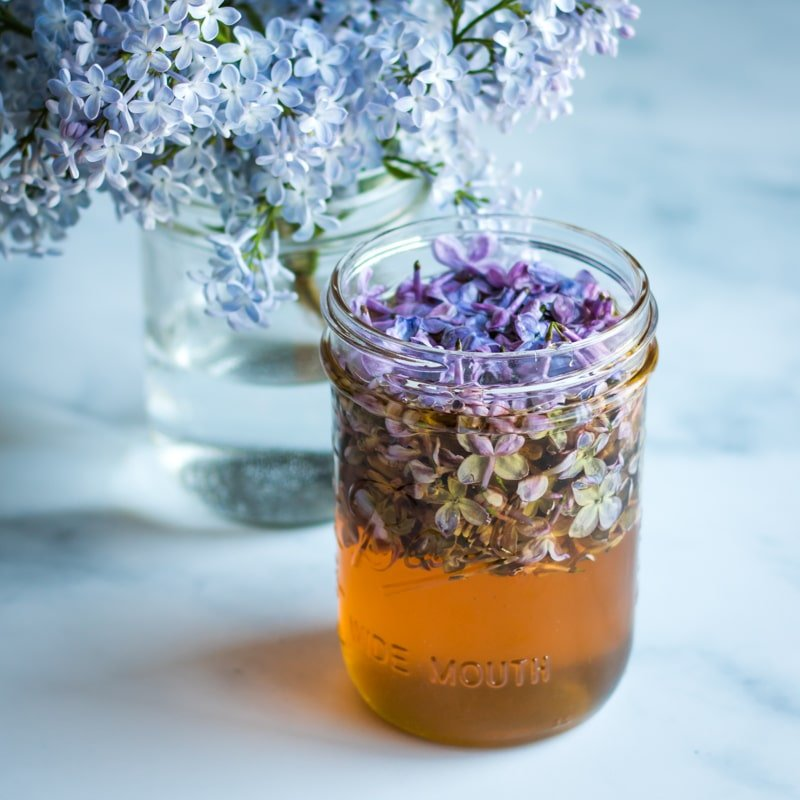 a jar showing the lilac blossoms floating to the top of the honey