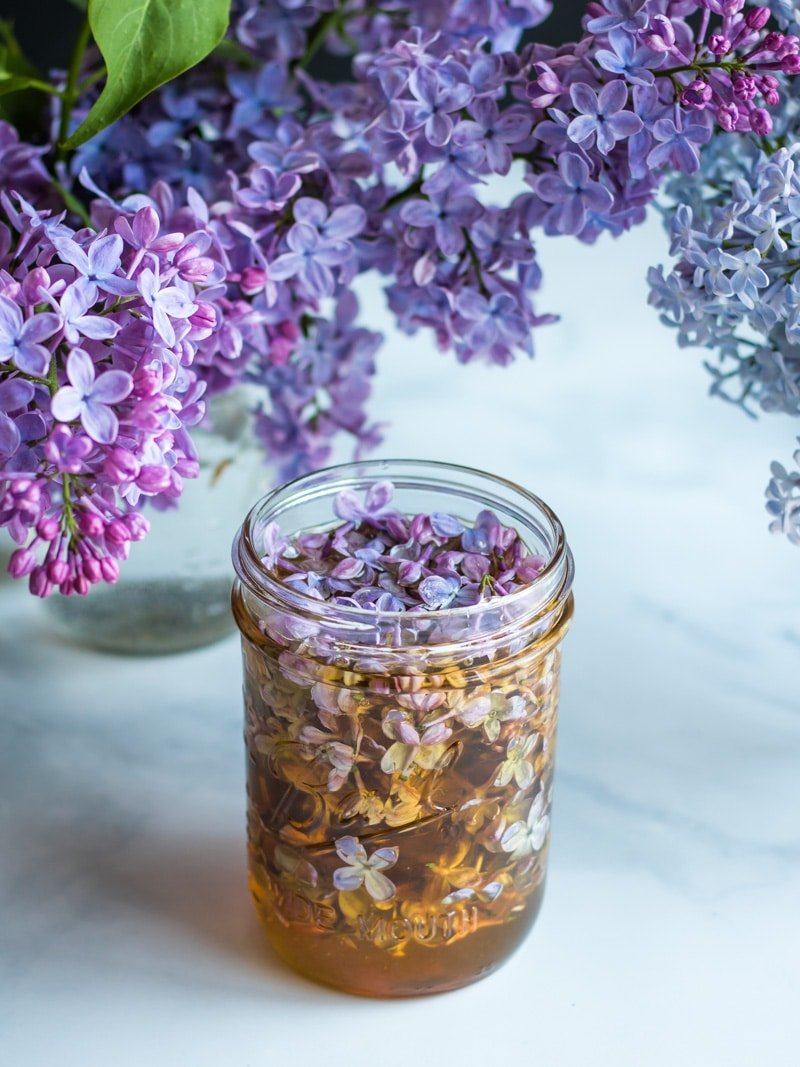 a jar of lilac infused hone with lilac flowers all around