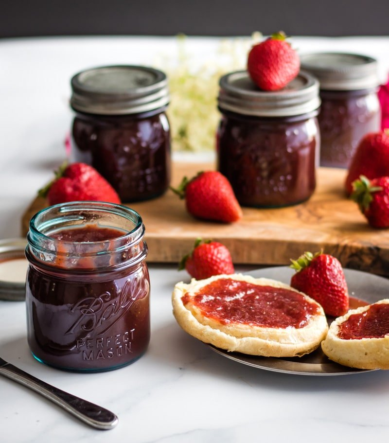 an open jar of strawberry honey butter and an english muffin