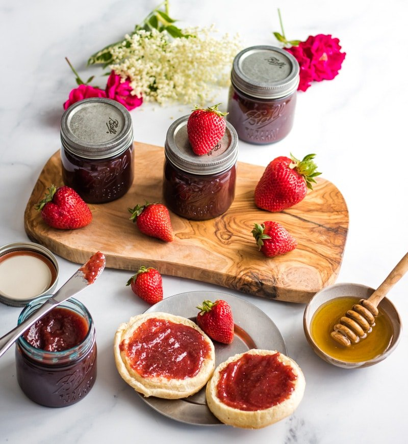a breakfast scene with jars of strawberry butter