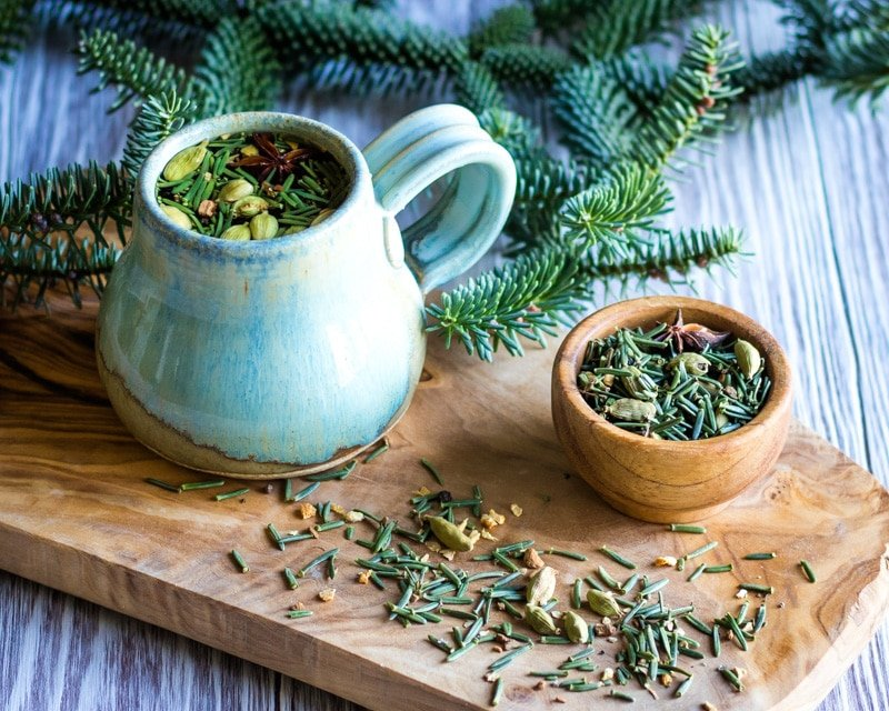 a mug and small bowl of fir needle chai